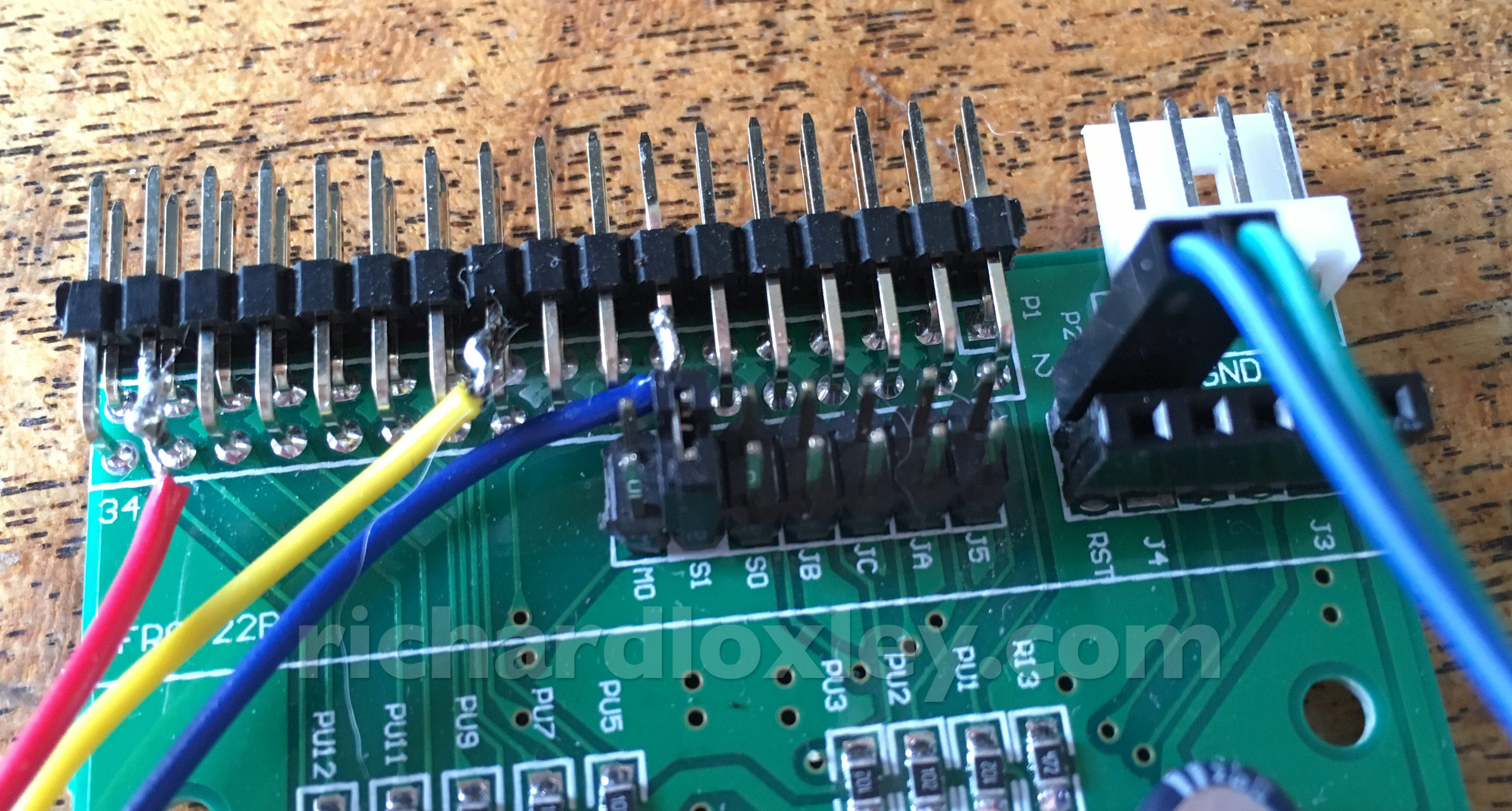 The black pins at the top left are the 34 pin floppy interface. The 4 white pins  at the top right are the power connections.